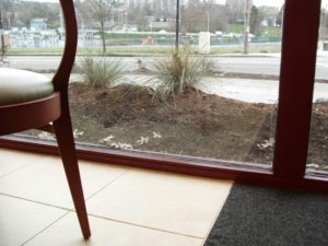 """Just keep piling on the mulch. The windows will keep it in place"". This planting bed was not intended to be a berm."